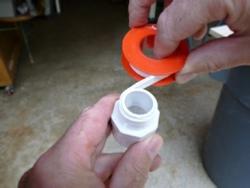 applying teflon tape to rain barrel fitting